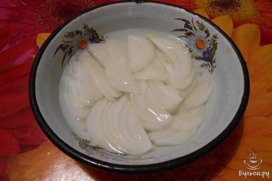 Лук почистить и нарезать полукольцами. Залить минеральной водой и уксусом 1:1. Оставить на 15 минут. Откинуть на дуршлаг и дать стечь маринаду.