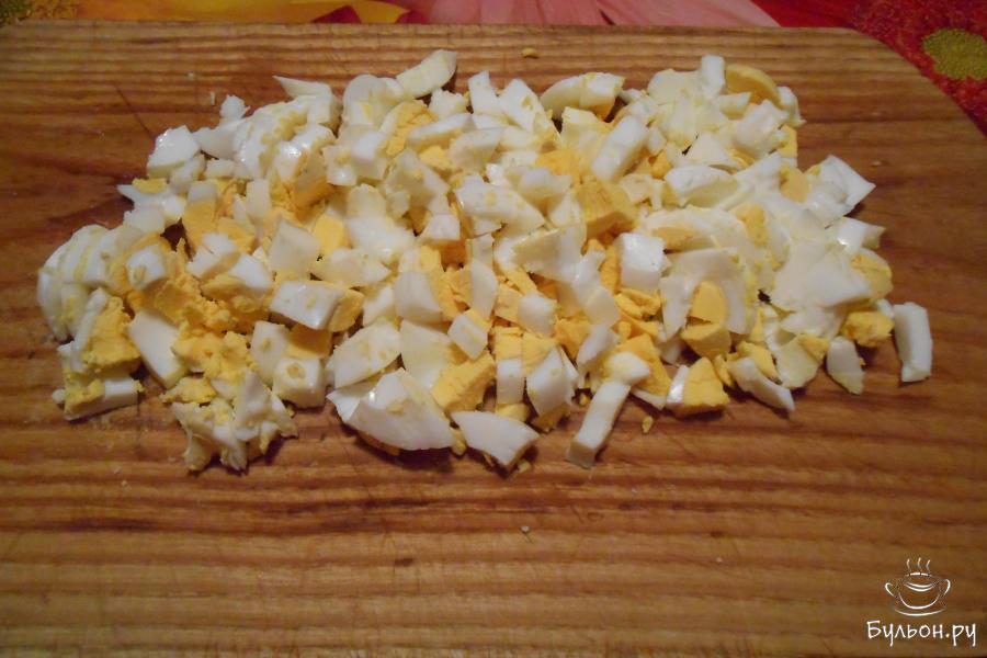 Яйца почистить и нарезать кубиками.