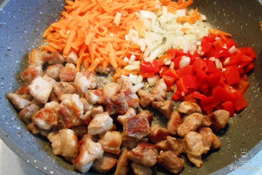 Добавить овощи к мясу и долить 2 столовые ложки растительного масла. Перемешать и жарить на среднем огне 7 минут, помешивая.