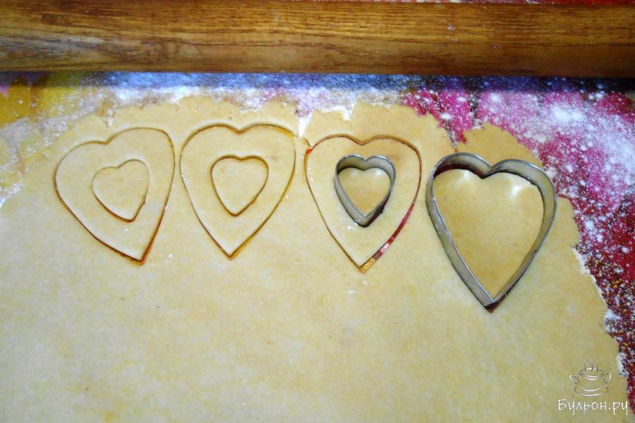 Вторую часть теста раскатать и вырезать такое же количество больших сердец, формой для печенья меньшего размера вырезать серединку. Получились ободки.