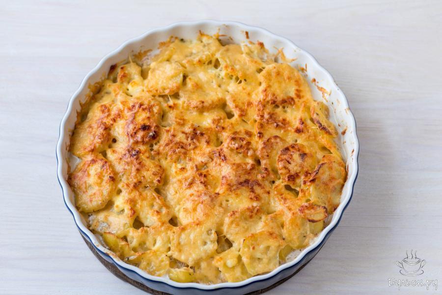 """Поместите блюдо в верхнюю треть духовки, увеличьте температуру до 200-220 градусов или включите режим """"гриль"""" и готовьте картофель еще 10-12 минут, пока сыр не подрумяниться."""