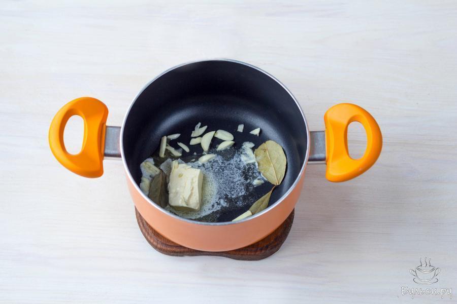 На небольшом огне растопите 1 столовую ложку сливочного масла. Добавьте 2 мелко нарезанных зубчика чеснока и 2-3 лавровых листа и помешивая, обжарьте чеснок 2-3 минуты.