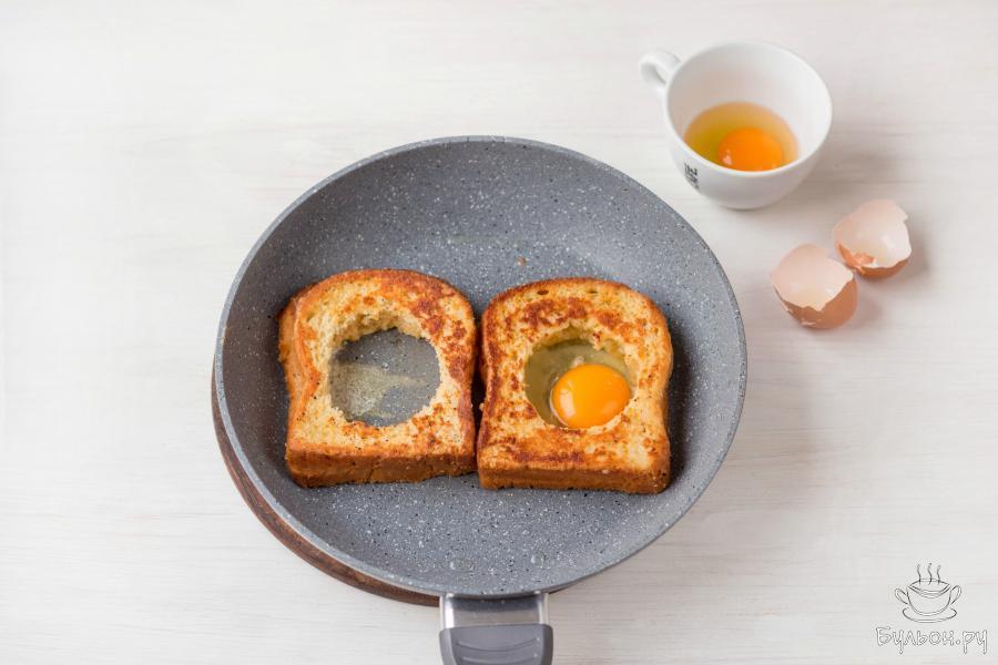 Разбейте яйцо в неглубокую чашку. Затем осторожно, стараясь не повредить целостность желтка, влейте яйцо в отверстие в хлебном мякише.