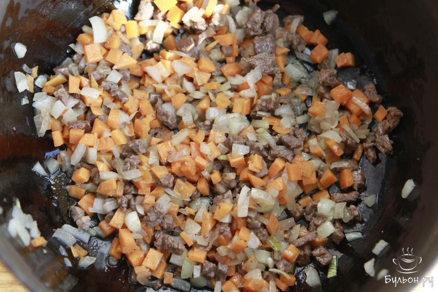 В казане разогреть растительное масло и обжарить мясо, лук и морковь в указанной последовательности.