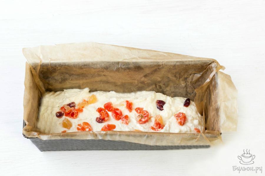 Выложите половину творожной массы в смазанную маслом и выстеленную пекарской бумагой форму для запекания. Добавьте подготовленные сухофрукты или цукаты, а затем добавьте оставшуюся часть творожной массы.