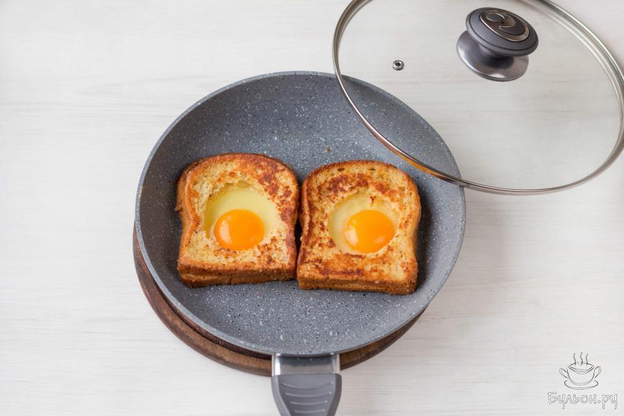 Прикройте сковороду крышкой и на небольшом огне готовьте блюдо еще несколько минут, до желаемой степени готовности яичного желтка.