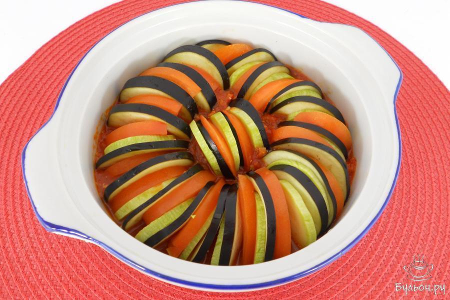 Томатный соус перелить в огнеупорную кастрюльку или форму для запекания. Чередуя овощи друг с другом, выложить их плотно по кругу в соус.