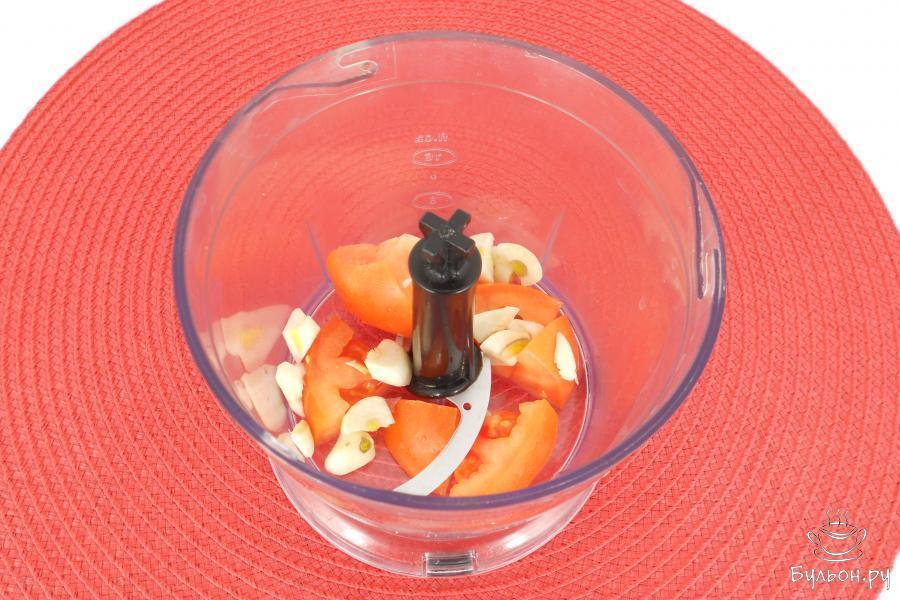 Один помидор порезать и поместить в чашу блендера вместе с двумя зубчиками чеснока.