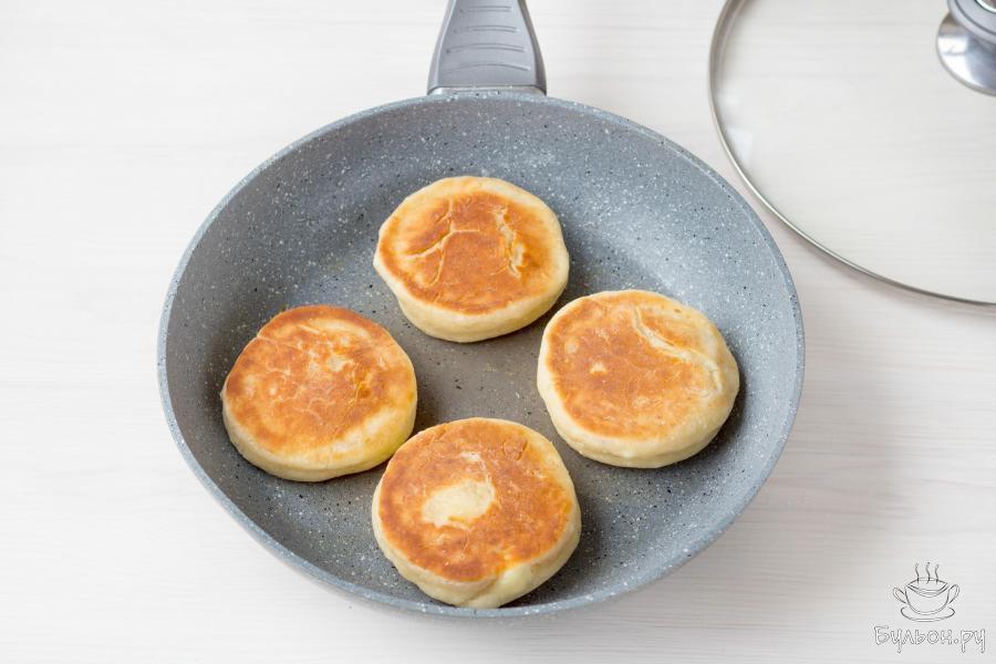 Затем переверните и обжарьте сырники еще 3-5 минут, с другой стороны. На этом этапе приготовления сковороду можно прикрыть крышкой.