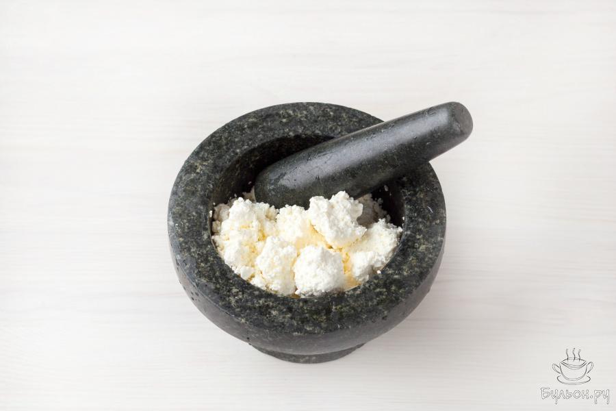 Протрите творог через сито, измельчите в блендере или разотрите при помощи ступки или толкушки для картофеля до пастообразного состояния.