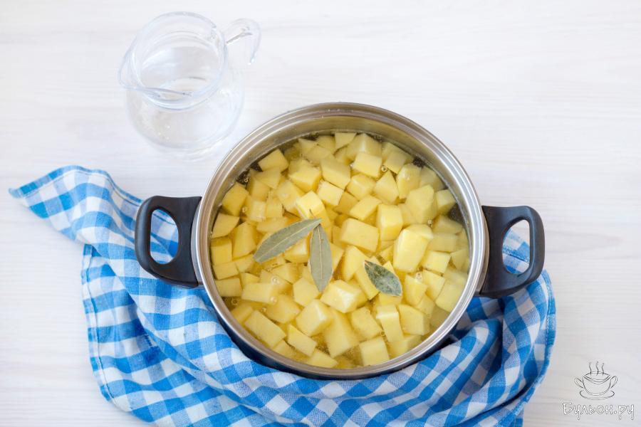 Добавьте очищенный и нарезанный небольшими кубиками картофель. Влейте воду и добавьте 2-3 лавровых листа.