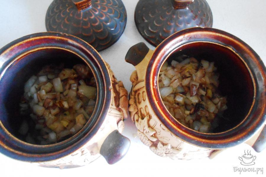 Уложить лук вторым слоем на мясо в горшочки поровну.