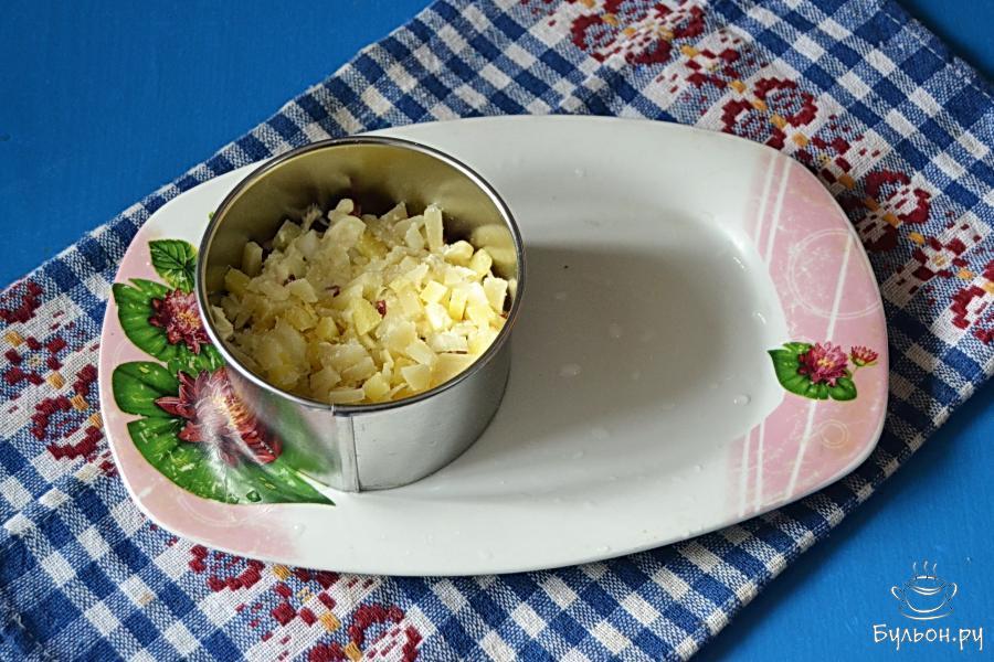 Картошку для салата приготовить заранее - отварить в мундире и почистить. Нарезать мелкими кубиками и выложить следующим слоем, посолить, промазать майонезом.