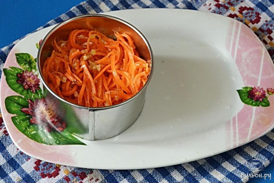 Далее - очередь корейской моркови. Отожмем с нее жидкую часть (уксус, масло), выложим на картошку и так же смажем майонезом.