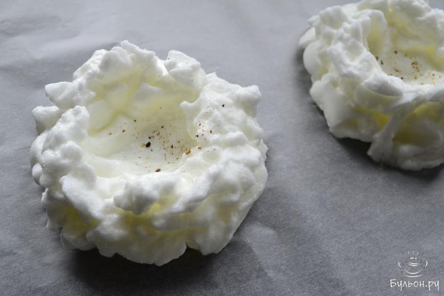 Противень застелить пергаментом и ложкой выложить белки на 2 порции, в виде красивых, пышных круглых облаков с углублением для желтков посередине. Посыпать немного черным перцем. Поместить белки в разогретую до 180-190 градусов духовку на 2-3 минуты.