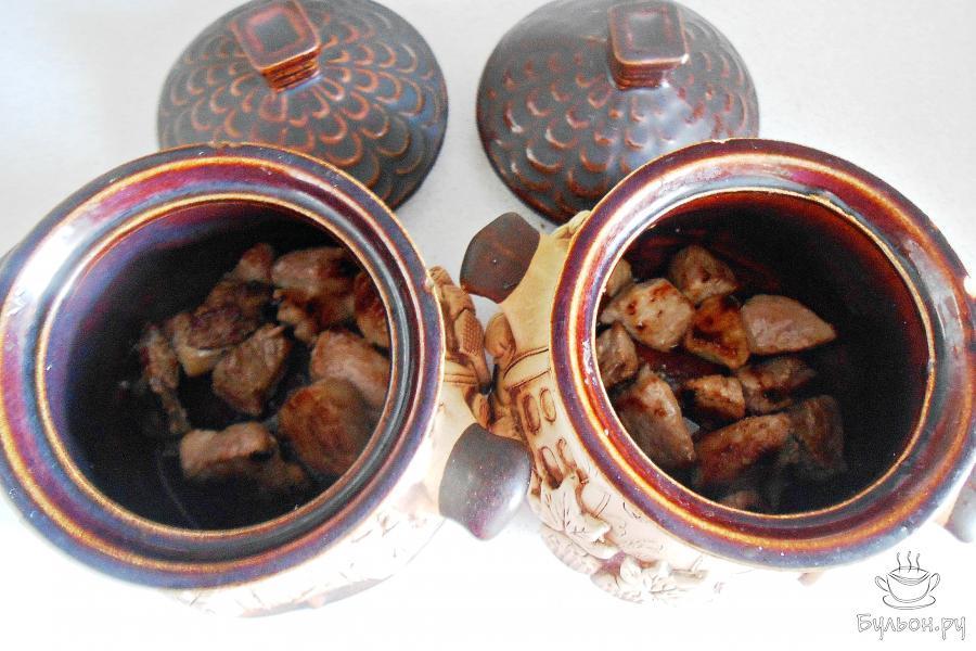 Переложить мясо в горшочки поровну.