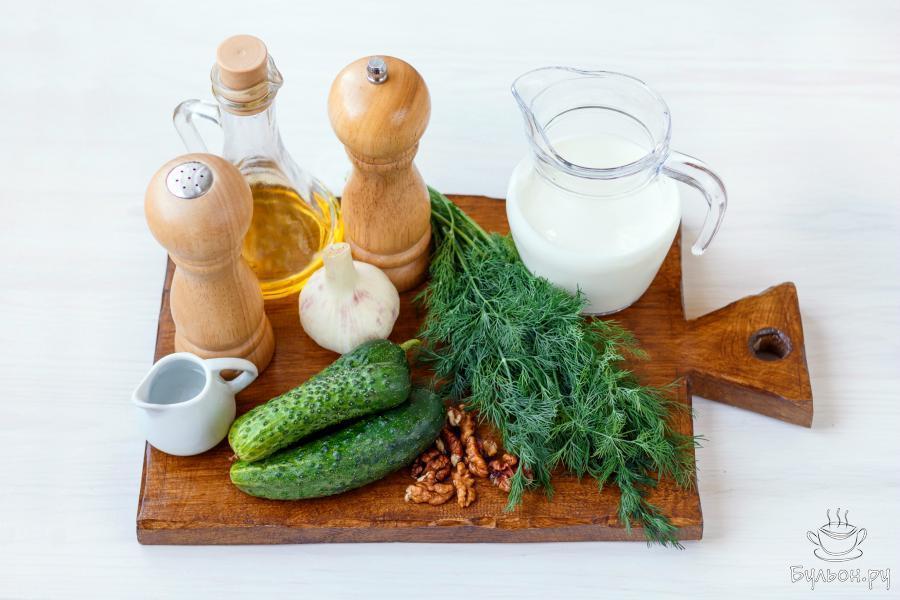 Для приготовления блюда вам понадобятся кислое молоко, йогурт или кефир. А также немного огурцов, пучок укропа, соль, молотый черный перец, несколько зубчиков чеснока, 2-3 столовые ложки оливкового масла, горсть поджаренных ядер грецких орехов, и по желанию, немного охлажденной питьевой воды.