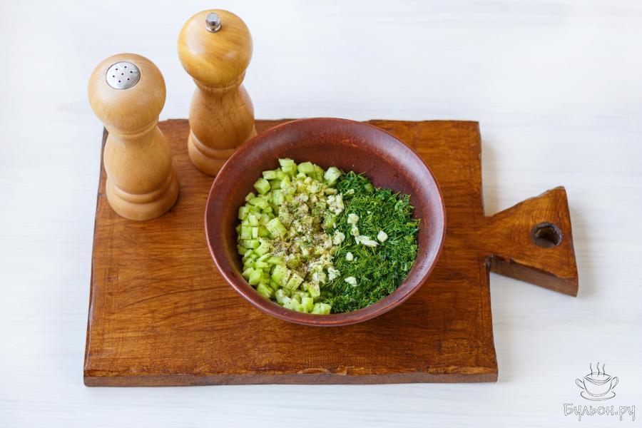 Соедините огурцы, чеснок и укроп. Добавьте несколько щепоток соли и молотого черного перца.