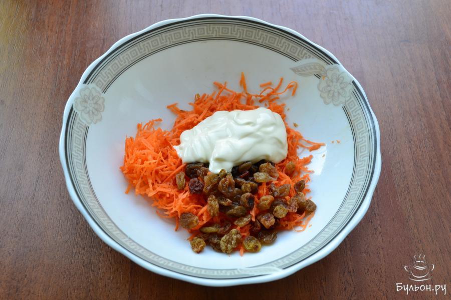 Морковь сырую почистить, на мелкой терке натереть в миску. Добавить изюм без косточек, предварительно замоченный в горячей воде и майонез.