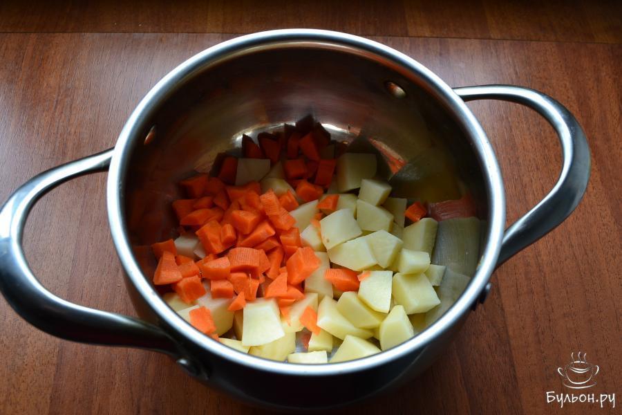 В кастрюльку нарезать средними кубиками очищенный и вымытый картофель и также порезанную морковку.