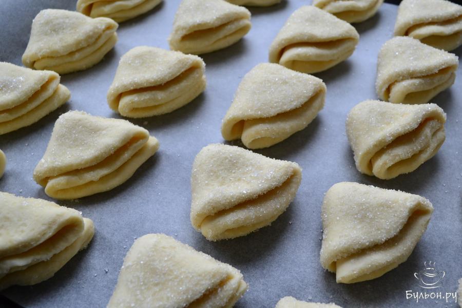 Свернуть лепешки пополам и снова пополам. Разместить печенье на выстланном пергаментной бумагой противне.
