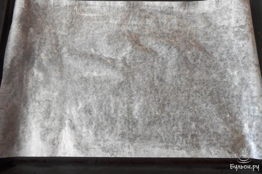 Первоначально подготовим поверхность для выпекания - противень застелим пергаментом и смажем маслом.