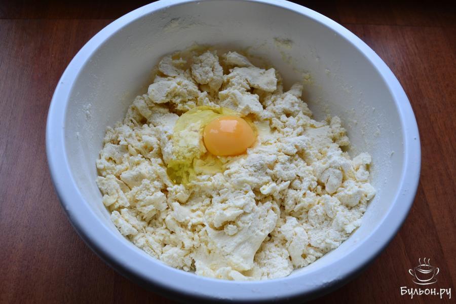Перетереть все вместе руками, чтобы получилась среднего размера крошка. Добавить сырое яйцо, тщательно тесто перемешать, добавить разрыхлитель и всыпать оставшуюся муку.