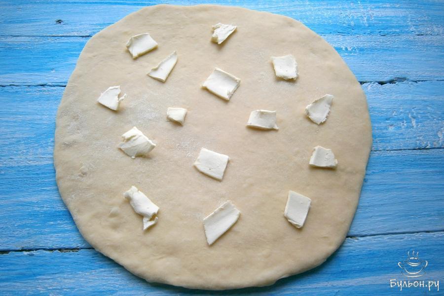 Затем тесто немного обмять, раскатать в лепешку, толщина которой около 0,5 сантиметров. По всей лепешке разложить маленькие кусочки сливочного масла.