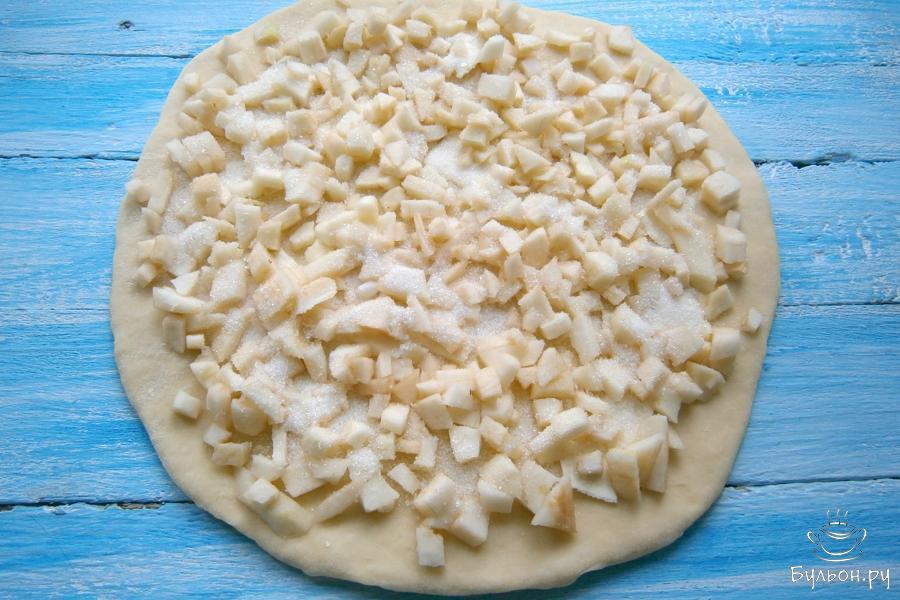 Лепешку из теста покрыть полностью яблоками, посыпать 2 столовыми ложками сахарного песка.
