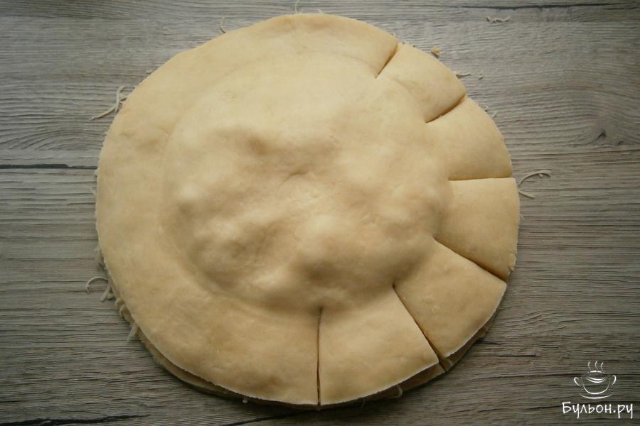 Накрыть все второй лепешкой из теста, чуть придавить. Далее, ножом сделать разрезы по краю, в части, где расположен сыр на расстоянии приблизительно 5 см, до фарша.