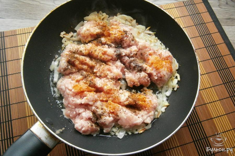 Лук обжарить до золотистости, затем выложить к нему куриный фарш. Посолить фарш, поперчить, посыпать любыми специями или приправой для курицы.