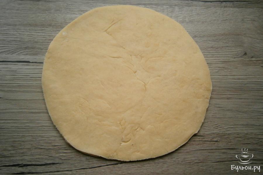 Подошедшее тесто нужно разрезать на 2 части. Каждую часть скалкой раскатать в тонкую лепешку диаметром около 23-24 см. Ровно обрезать края разместив на лепешках подходящую тарелку или крышку.