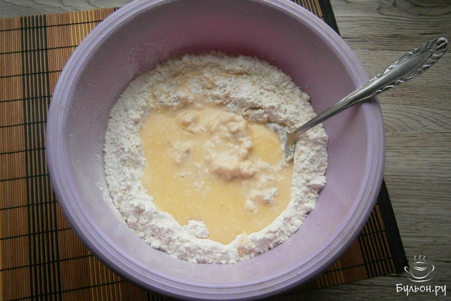 Постепенно вливать молочно-масляную смесь, замешивая тесто.