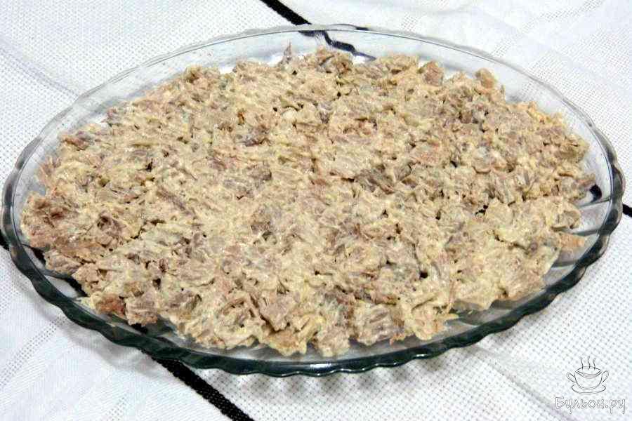 Кусок постного мяса отварить до готовности, минут 25-30, остудить. Затем нарезать кубиками, добавить немного майонеза и перемешать. Это нужно для того, чтобы мясо не распадалось при разделении на порции готового салата. Далее выложить мясо на блюдо - это первый слой нашего салата.