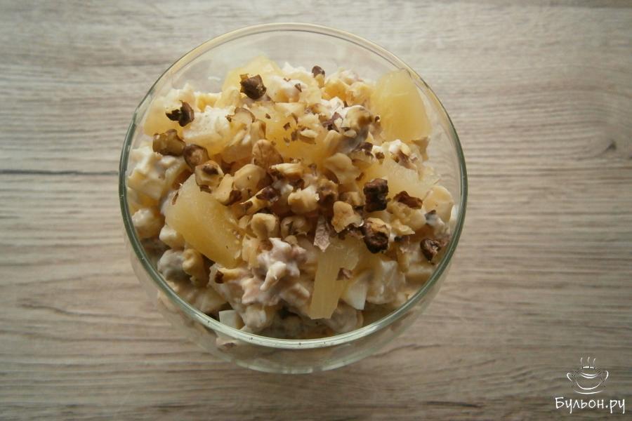 Салат переложить в креманку или в небольшой салатник, посыпать сверху рубленными ножом ядрышками грецких орехов.