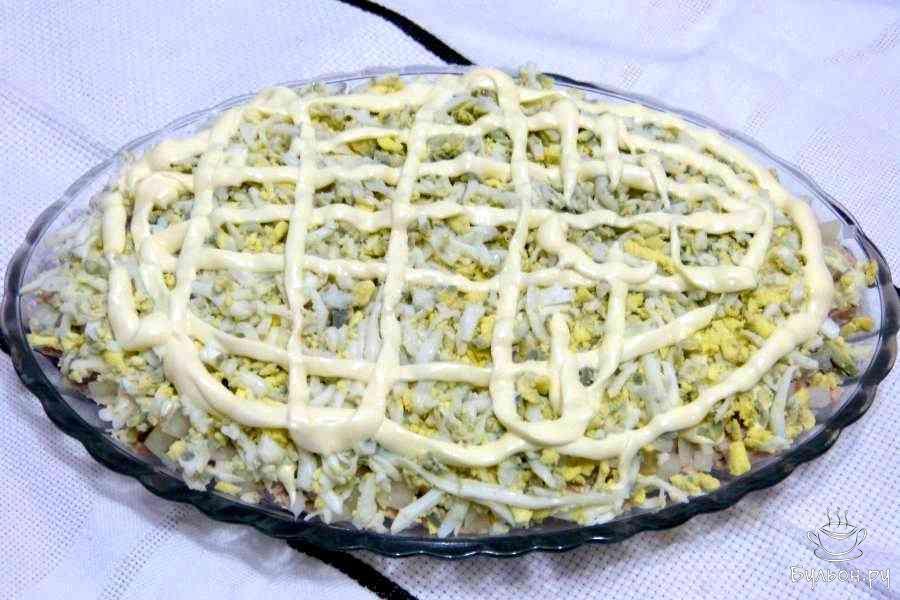 Третий слой - яйца. Отварить, почистить, от яйца отрезать кружок для украшения, остальные натереть на крупной терке прямо на лук, также сделать сетку из майонеза.