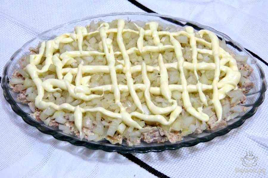 Второй слой - лук. Почистить, порезать мелкими кубиками, сложить в глубокую миску, залить уксусом на 30 минут, затем слить всю жидкость, выложить на мясо и сделать майонезную сетку.