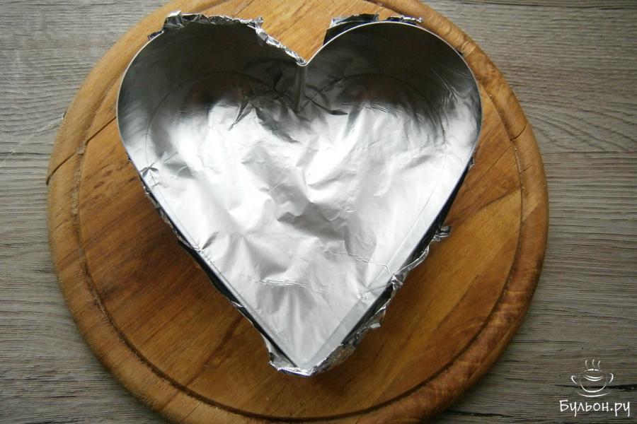 Формочку в виде сердца, только меньшего диаметра, чем для бисквита, снизу затянуть фольгой. Форму поместить на досочку.