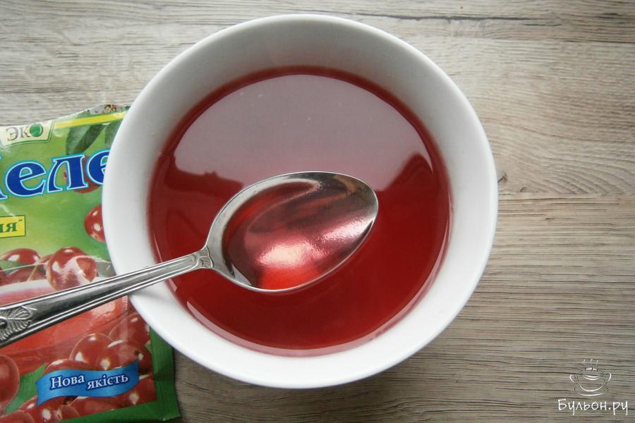 Пачку любого фруктового или ягодного желе, желательно, чтобы получилось красного цвета, развести по инструкции кипятком, только количество кипятка нужно уменьшить на 100 мл. Жидкое желе остудить.