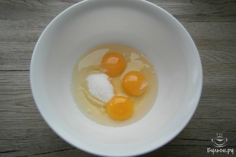 3 сырых яйца разбить в миску, всыпать щепотку соли, 100 г сахарного песка и 1 ч. л. ванильного сахара.