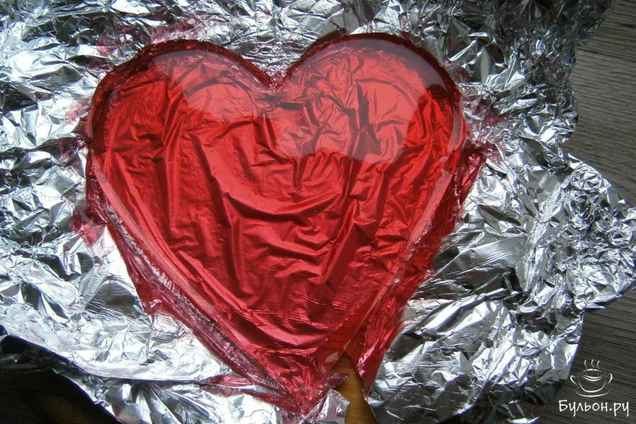 Достать из холодильника застывшее желе, освободить его от формочки, оставив в фольге.