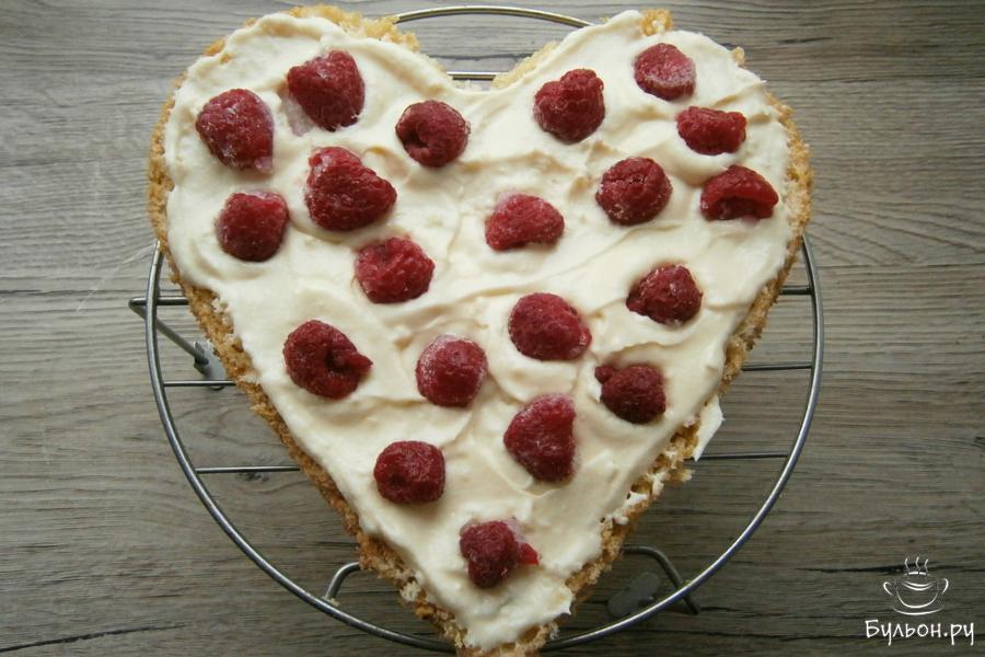 Нижнюю часть бисквита промазать половиной крема, выложить ягоды малины. Можете использовать и клубнику, вишню и т. д. Малина у меня была замороженной.