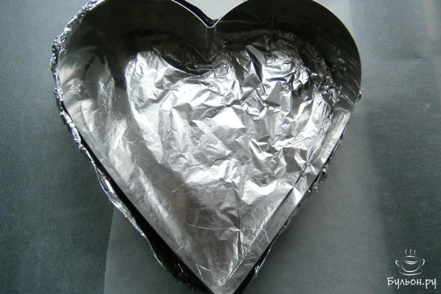 Форму в виде сердца диаметром приблизительно 22 см поместить на противень. Если формочка без дна, как на фото, затянуть его фольгой.