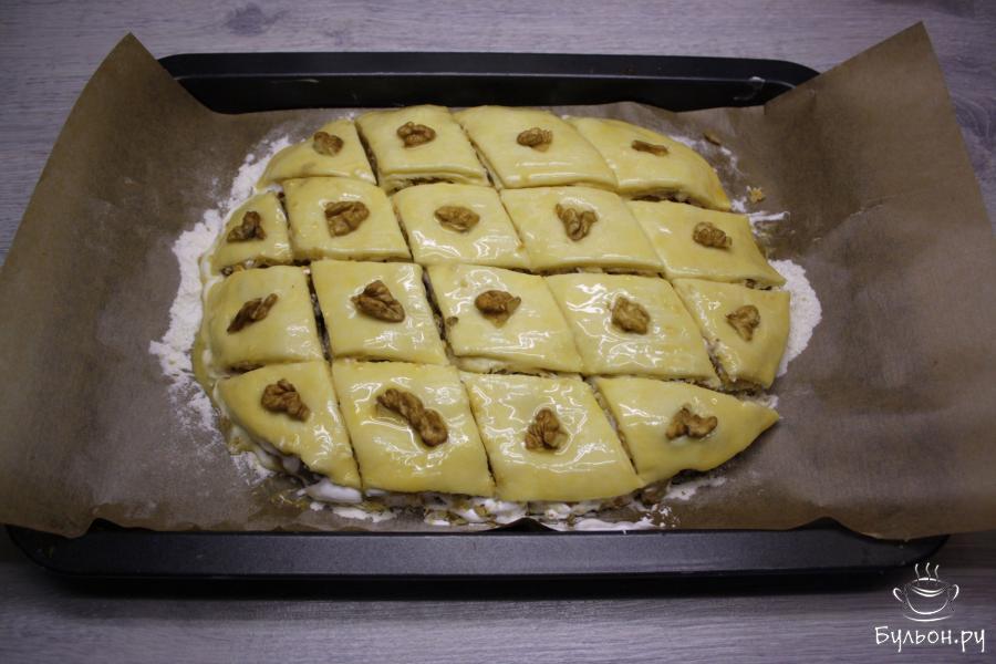 Сверху аккуратно положить выпеченный корж и нанести оставшуюся начинку. Затем еще один пласт теста. Смазать поверхность сырым яйцом. Пахлаву в сыром виде аккуратно разрезать на ромбики. Украсить кусочками гречкого ореха.