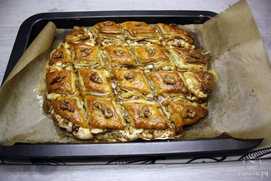 Готовый горячий пирог пропитать жидким медом, проливая все отверстия между кусочками.
