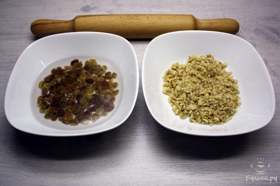 Для начинки грецкие орехи измельчить в крошку с помощью скалки или блендера. Изюм замочить в теплой воде.