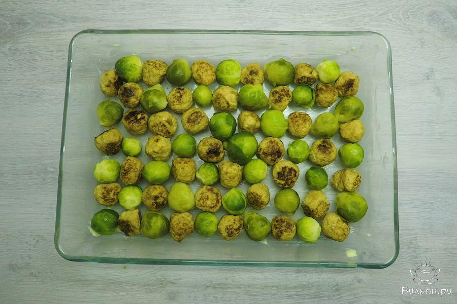 Форму для запекания смазать сливочным маслом. Нижним слоем выложить кочанчики брюссельской капусты и мясные фрикадельки.