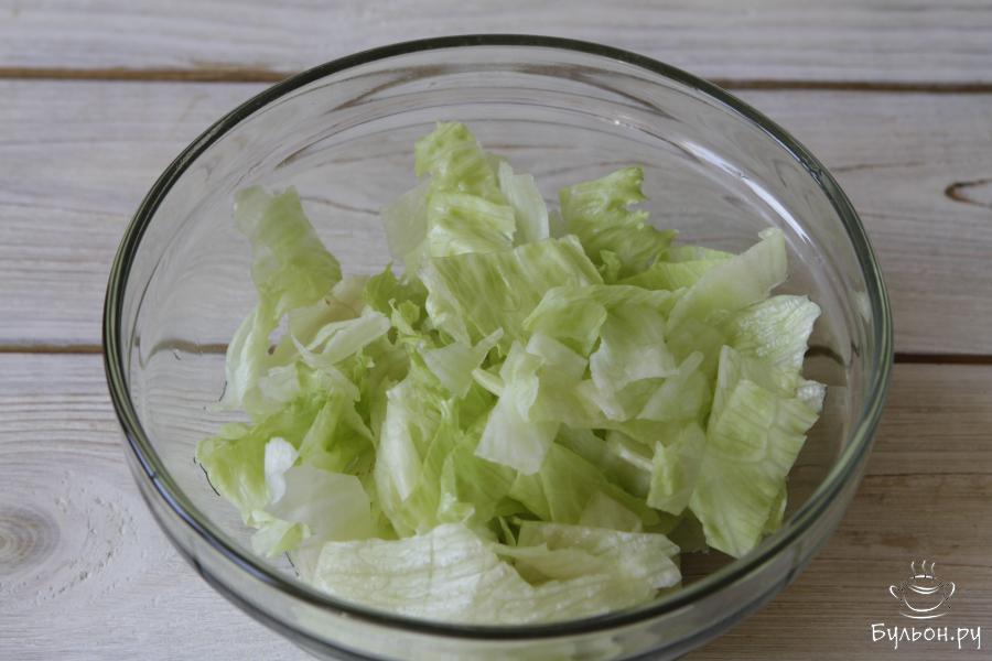 Листья салата айсберг тщательно промыть, обсушить и мерло нарезать, а еще лучше порвать.