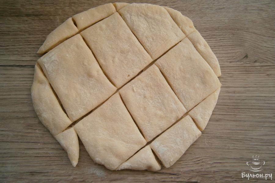 Далее, тесто чуть обмять, разделить его на части. Каждую часть раскатать в небольшую лепешку, толщина которой должна быть не менее 1 см. Тесто порезать средними ромбами.