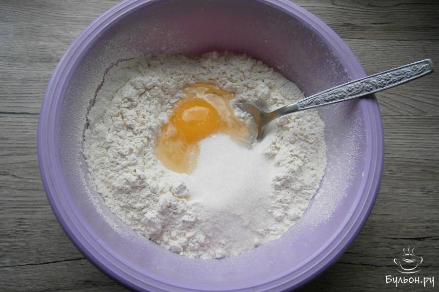 В муку добавить куриное сырое яйцо, щепотку мелкой соли, сахарный песок и соду.
